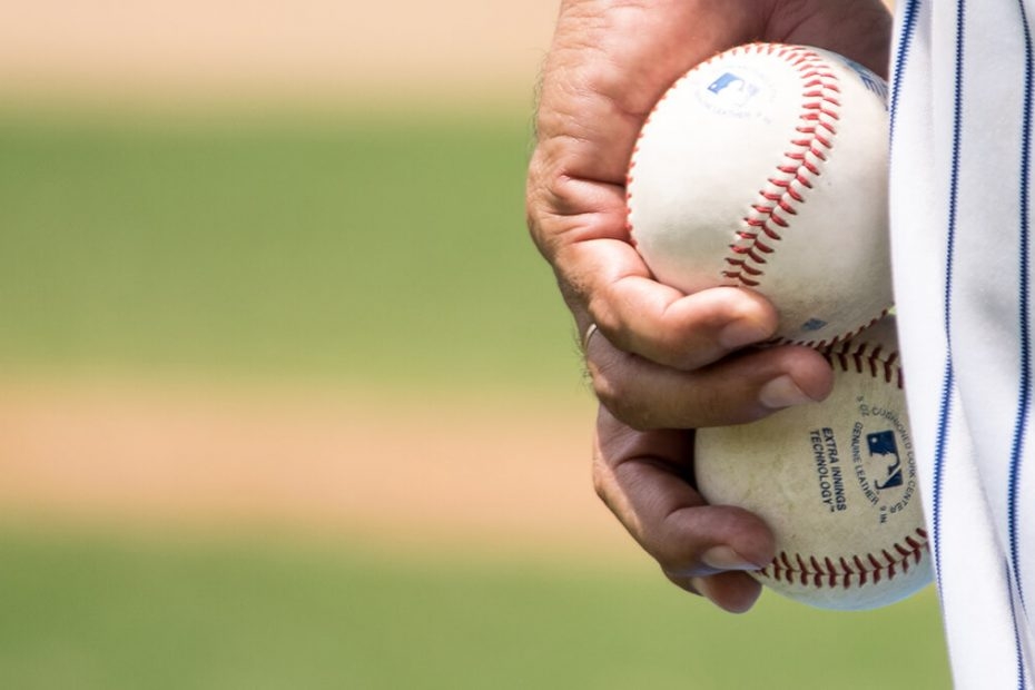 Account coverage - Man with two baseballs in his hand