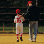 Coach your teams a coach with a young baseball player