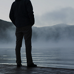 Man is suit looking over water and fog