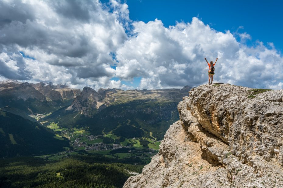 Woman standing on a cliff edge with her arms raised in victory.